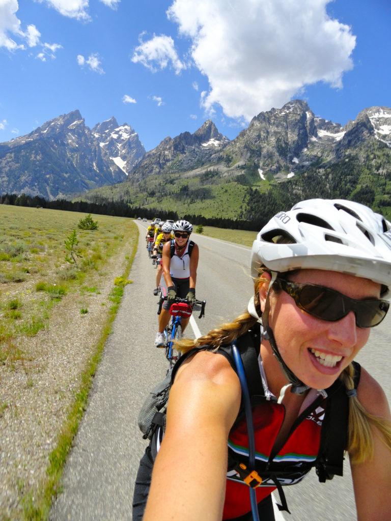 a group of people are cycling on the road around Yellowstone National park
