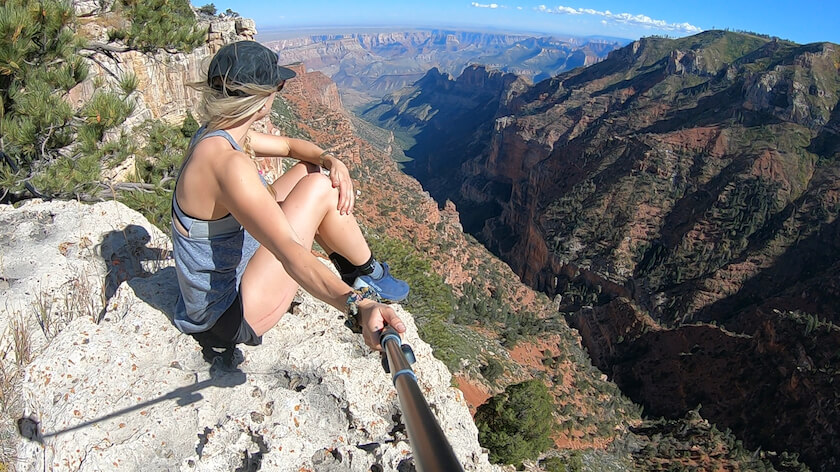 a girl is sitting on a cliff holding her selfie stick