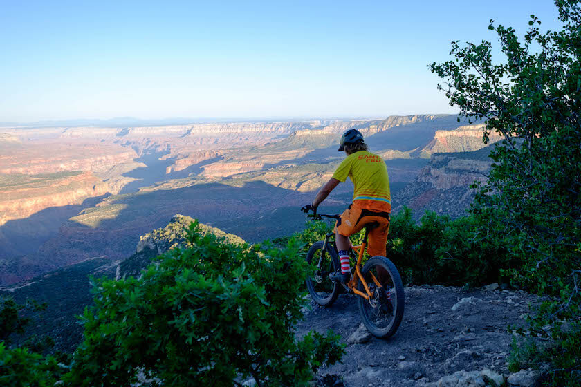 a man on his bicycle is standing on a mountain looking the view of the valley